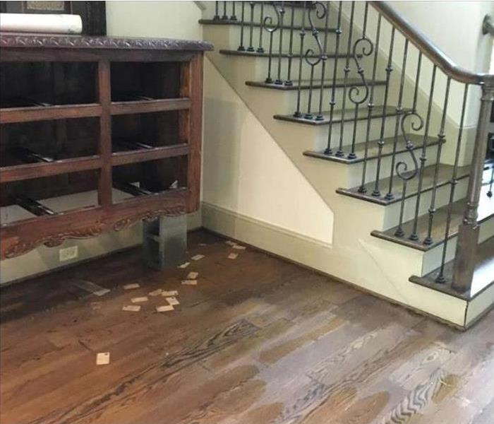 water damaged planked flooring and staircase walls