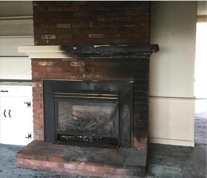 brick fireplace charred mantle and side white cabinets dirty from soot