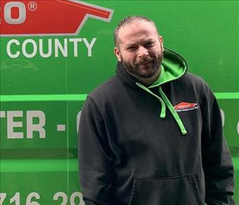 A male employee standing in front of a SERVPRO vehicle.